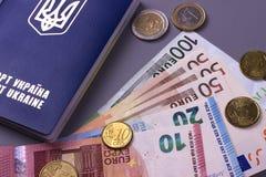 Passeport ukrainien international avec d'euro billets de banque d'isolement sur le fond gris Photos libres de droits