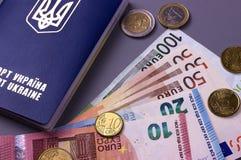 Passeport ukrainien international avec d'euro billets de banque d'isolement sur le fond gris Photo stock