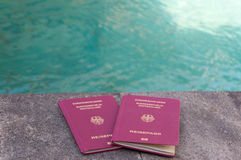 Passeports allemands devant l'eau de turquoise Photo libre de droits