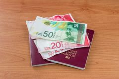 Passeports biométriques avec de nouveaux billets de banque israéliens de shekel images libres de droits
