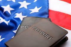 Passeports dans des couvertures en cuir sur le drapeau photo stock