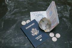 Passeports des USA et petit globe en verre sur le fond noir Photo libre de droits