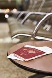 Passeports et billets pour le vol sur la chaise dans l'aéroport Images stock