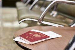 Passeports et billets pour le vol sur la chaise dans l'aéroport Photographie stock libre de droits