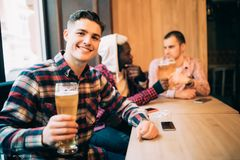 Passer le temps avec des meilleurs amis Jeune homme beau grillant avec de la bière et souriant tout en se reposant avec ses amis  photos libres de droits