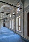 Passera i den Nuruosmaniye moskén med kolonner, bågar, och golvet som täckas med blått, mattar tänt av sidofönster, Istanbul, Tur Arkivfoto