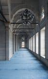 Passera i den Nuruosmaniye moskén med kolonner, bågar, och golvet som täckas med blått, mattar tänt av sidofönster, Istanbul, Tur Royaltyfri Bild