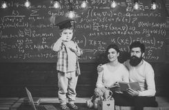 Passerandeexamenbegrepp Smart barn i övre gest för doktorand- lockshowtumme Pojke som framlägger hans kunskap till mamman och far Arkivfoton