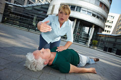 Passerby asking for First Aid help. Passerby with unconscious senior women asking for First Aid help Royalty Free Stock Images