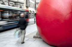 A Passerby and a bus go passed a giant red ball. A Passerby and a bus go passed Kurt Perschke's giant Red Ball that was squeezed into the entrance of the Royalty Free Stock Photography