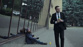 Businessman giving money to homeless. Passerby businessman walking and giving some money to homeless person Stock Image