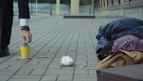Passerby giving money to beggar Royalty Free Stock Images