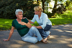 Passerby helping senior woman Stock Photography