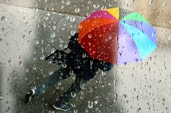 The passerby with the rainbow umbrella. royalty free stock photo