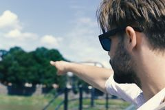 Passerby with serious face helps to find way or demonstrates view, defocused. Man looking aside and pointing far. Guy. With sunglasses shows direction stock photos