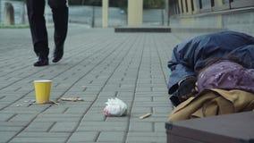 Passerby som ger pengar till tiggaren lager videofilmer