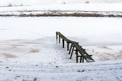 Passerella di legno in uno stagno nevoso congelato negli altopiani Fotografia Stock