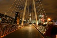 Passerelle au-dessus de fleuve la Tamise par nuit Photos stock