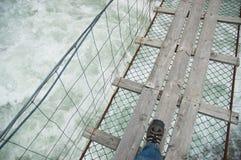 Passerelle de corde au-dessus de l'eau sauvage Photographie stock libre de droits