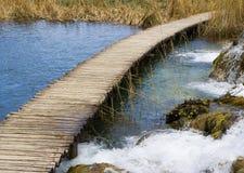 Passerelle en bois au-dessus d'un fleuve Photos stock
