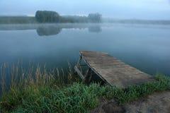 Passerelle en bois menant à un lac Photographie stock libre de droits