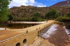 Passerelle en pierre à travers la petite rivière Image stock