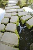 Passerelle en pierre au-dessus d'un flot Photographie stock libre de droits
