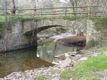 Passerelle en pierre au-dessus de fleuve images stock