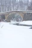 Passerelle en pierre au-dessus de flot en hiver Image libre de droits