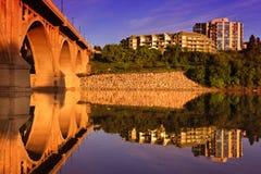 Passerelle relecting dans le fleuve calme Photos stock