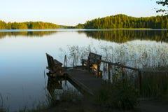 Passerelle vide avec un banc sur un lac au lever de soleil Photographie stock libre de droits