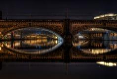 Passerelles au-dessus du fleuve la nuit Photographie stock