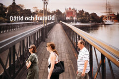 Passers-by on the background of a huge banner with Royalty Free Stock Images