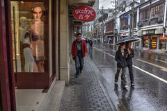 Passers flow along wet pavementwalked past store on city street. Stock Photography