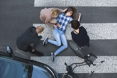 Passersby helping casualty of a car accident. Passersby helping an unconscious casualty of a car accident lying next to the bike stock images