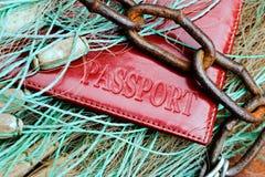 Passet ligger på ett fisknät och tilltrasslat med en rostig kedja Begreppet av bestraffningen för olagligt fiska och royaltyfri bild