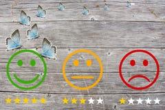 Passez en revue la classification avec les visages heureux et fâchés sur le fond et les étoiles en bois Image stock