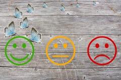 Passez en revue la classification avec les visages heureux et fâchés sur le fond en bois Photographie stock libre de droits