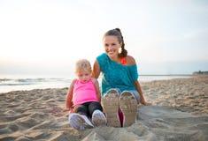 Passform, lyckligt barn moder och dotter i genomkörarekugghjul på stranden Arkivfoto