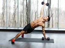 Passform muskulös idrotts- ung man som är shirtless i sportswearen som gör styrkaövning med hantlar i idrottshall royaltyfri fotografi