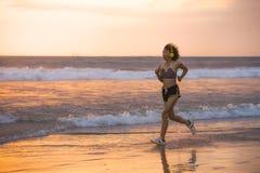 Passform och idrotts- asiatisk kinesisk sportig kvinna som kör på den härliga stranden som gör jogga genomkörare på solnedgång i  fotografering för bildbyråer