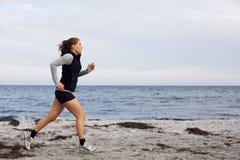 Passform och sund spring för ung kvinna längs shoreline royaltyfria bilder