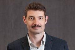 Passfoto eines lächelnden Vierzigermannes mit einem kurzen Schnurrbart Stockbild
