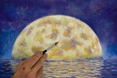 Passi con la pittura della spazzola una grande luna arancio in blu, la riflessione della luna in oceano, il mare, l'acqua fotografia stock
