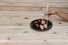 Passi i bastoncini dei sushi della tenuta su un fondo di legno della tavola della banda nera Immagine Stock