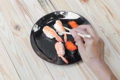Passi i bastoncini dei sushi della tenuta su un fondo di legno della tavola della banda nera Immagini Stock