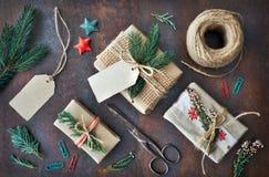 Passi i regali elaborati su fondo scuro con le decorazioni di Natale Fotografia Stock