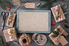 Passi i regali elaborati sulla tavola di legno rustica con il decorat di Natale Immagine Stock