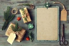 Passi i regali elaborati sulla tavola di legno rustica con il decorat di Natale Fotografia Stock Libera da Diritti
