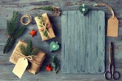 Passi i regali elaborati sulla tavola di legno rustica con il decorat di Natale Fotografie Stock Libere da Diritti